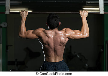 Young Athlete Doing Pull Ups - Male Athlete Doing Pull Ups -...