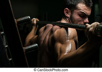 Barbell Squat - Young Man Performing Barbell Squats - One Of...