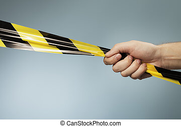 Barrier tape - Man holding a yellow and black plastic...