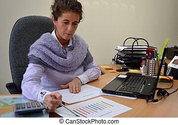 Frau im Buero - Angestellte prueft Bilanz