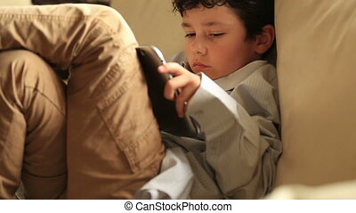 smart kid with digital tablet - little boy relaxation with...