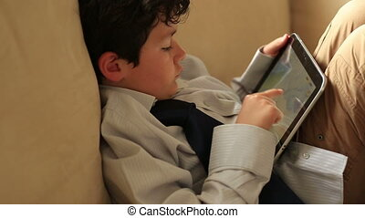 smart kid with digital tablet - little boy playing digital...