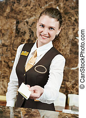 hotel worker with key card - smiling female receptionist...