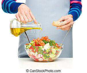 Cook is pouring olive oil into salad - Cook is pouring olive...