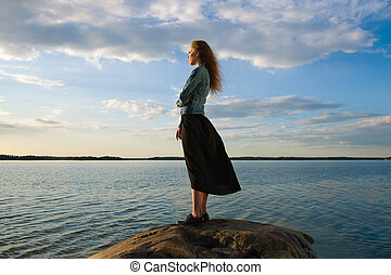 Woman looks at the horizon - Beautiful young woman looks at...