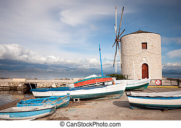 small port with fish boats and a windmill in the town of...