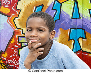 Young Afro boy in front of a wall - Young Afro boy in front...