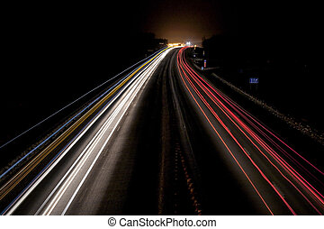 night winter highway with light lines from passing cars