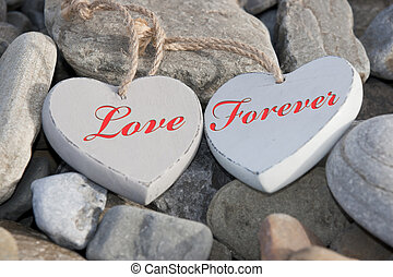 two love hearts on a rocky beach as one - two wooden love...