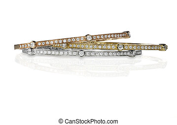Set of three colored gold and diamond bracelets stacked...