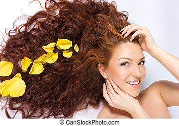 In yellow rose petals - Girl with long red hair lying on the...