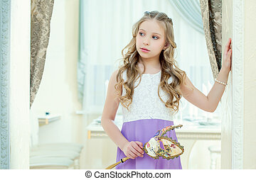 Little blue-eyed model posing with masquerade mask, close-up