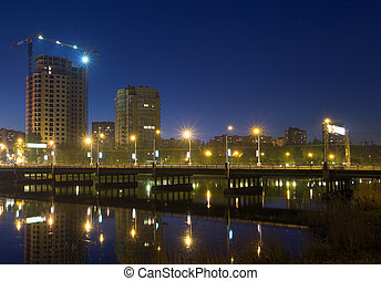 Night scene with illuminated bridge over river in Donetsk -...