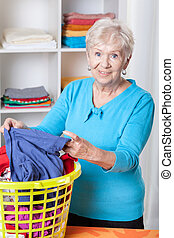 Elderly woman sorting laundry - Smiling elderly woman...