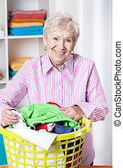 Sorting laundry - Smiley elderly woman sorting laundry at...