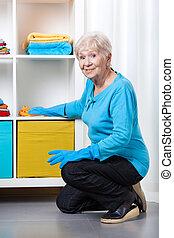 Elderly woman dusting shelves