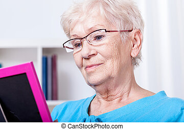 Elderly woman looking at photography