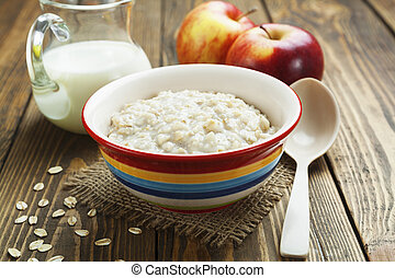 Oatmeal  - Porridge, oats, milk and red apples on the table