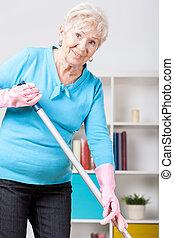 Elderly woman sweeping floor - Smiley elderly woman sweeping...