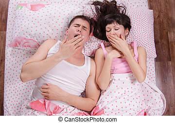 Young couple in bed morning yawning