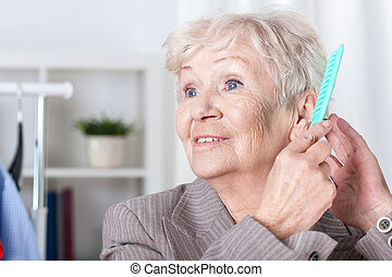 Elderly woman combing hair