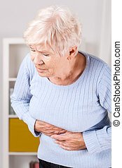 Stomachache - Portrait of elderly woman having stomachache...