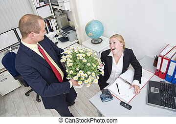 Business gift - Senior manager giving his younger female...