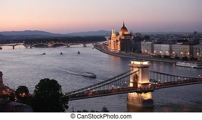 Tourist boats passing under Chain Bridge on Danube river...
