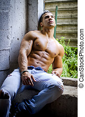 Muscular young latino man shirtless in jeans sitting against...