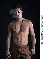 Athletic shirtless young man with mustache smoking -...