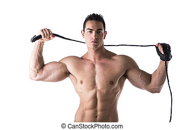 Muscular shirtless young man with whip and studded glove on...