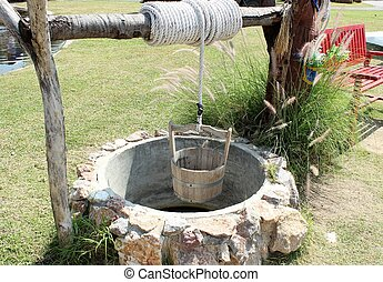 Water well - Antique water well of stone with bucket