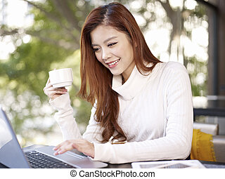 working in coffee shop - young woman using laptop computer...