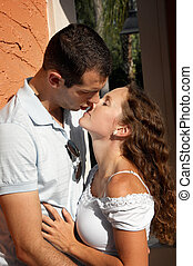 beautiful young lovers about to kiss in the afternoon sun