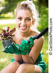 Planting flowers - Smiling young woman planting flowers in...