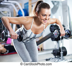 Young woman doing shoulder exercise - Cute Sporty young...