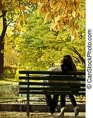 Romantic couple sitting in the autumn park