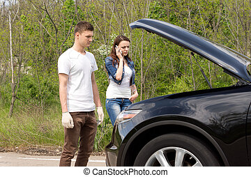 Young couple phoning for roadside assistance after their car...