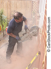 Using a disc cutter - A window fitter using a disc cutter on...