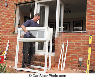 Window fitter at work - A Window fitter removing old windows...