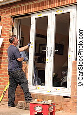 Window fitter at work - A window fitter fitting new doors...