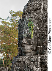 Stone face in ancient Bayon temple, Angkor in Cambodia -...