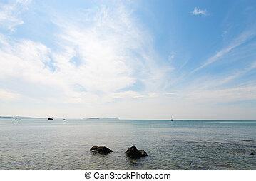 Stratus clouds in blue sky under calm sea
