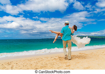 happy bride and groom having fun on a tropical beach