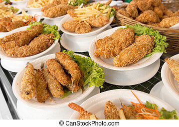 Deep fat fried food assortment in plates on cafe shop shelf