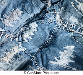 Heap of torn and frayed, threadbare jeans