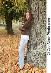 woman against tree - one young attractive redhead woman...