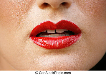 Lips - Close-up of a woman wearing bright red lipstick.