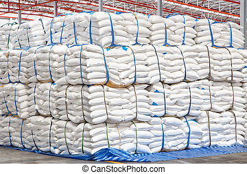 stacked sacks of meal in warehouse waiting for...