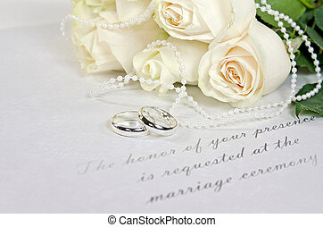 white roses and rings on invitation